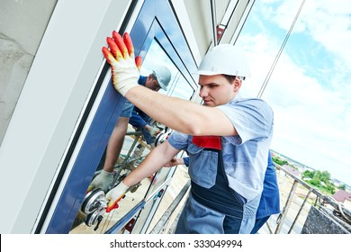 Two builders worker installing glass windows on facade of business building using glass suction plates