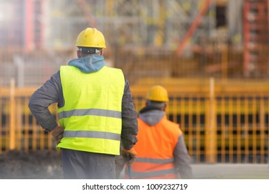 Two builders in yellow and orange at the construction site
