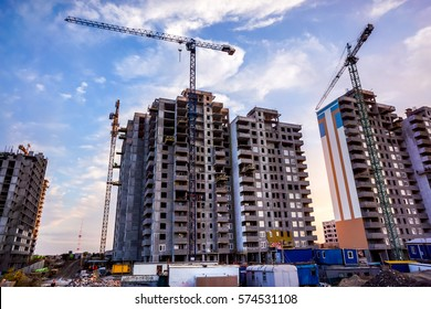 two building cranes at the background of a multi-storey building under construction with some small workers building in front of them against sunset sky. New houses will wait for families
