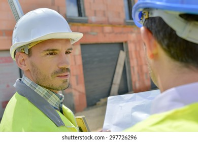Two building designers chatting on site