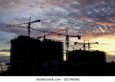Two building under construction in silhouette during sunset