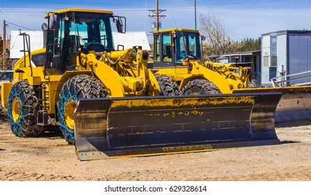 Two Bulldozers With Snow Tires In Springtime