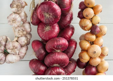 Two bunch of onion (sweet red onions and yellow onions) and bunch of garlic.