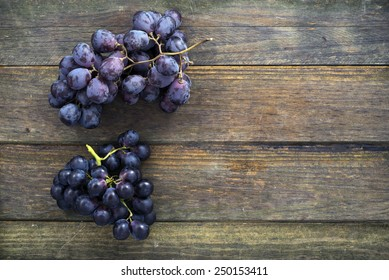 two bunches of black grapes on an old wooden table. Space for text