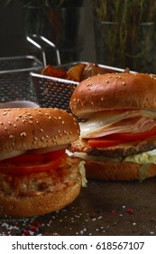 Two burgers with French fries and ketchup. The table is decorated with spices and cutlery on a dark background