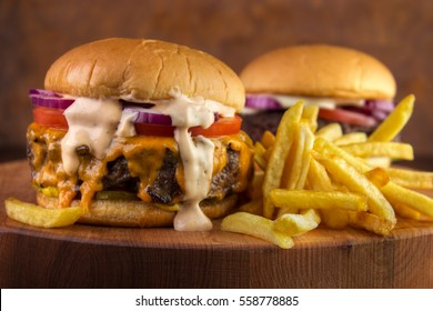 Two burgers and fries on wooden board , big half pound patty with melted real cheddar and lot of sauce