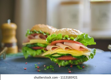 Two burgers with ham and cheese on the table - close-up