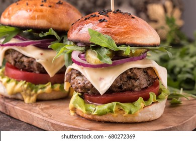 Two Burgers on a wooden board. Homemade Hamburger with Cheese and Lettuce.