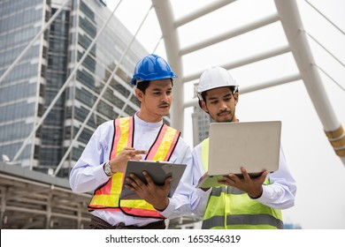 Two Burmese or Myanmar engineer workers with longyi traditional dress and helmet using computer laptop to check project plan or blueprint in Bangkok Modern city. Construction site Industrial concept.
