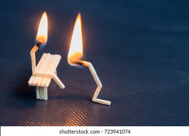 Two burning matches on black background. Husband apologizing wife. Man asking woman for forgivness. Boyfriend trying to convince girlfriend. Relationship problem.