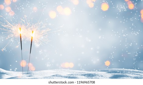 two burning sparklers in snow