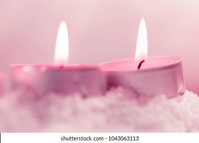 Two burning tealights in the snow