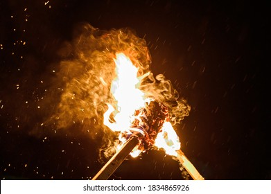 two burning torches on a dark background, smoke and fire from burning torches.