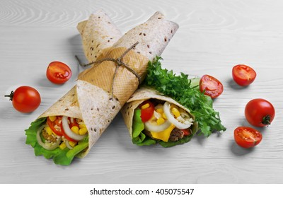 Two burrito wrapped in tortilla bread with cereals, corn, onion rings, lettuce, cheese, rosemary, pickled cucumbers, ketchup on a chopping board on a light white wooden background