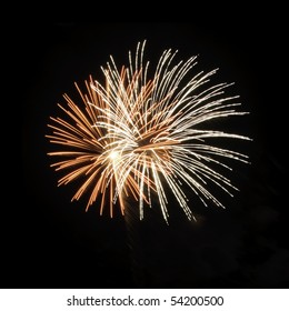 Two bursts of fireworks inside each other, one white, one reddish-orange with white-hot core