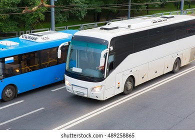 two buses go on the highway nearby