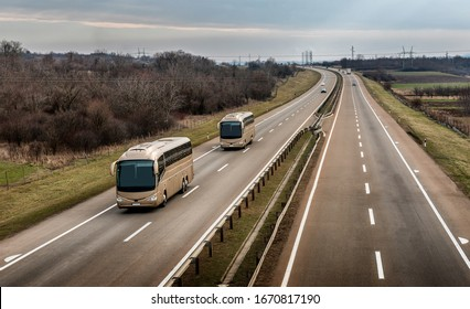 Two buses in line traveling on a highway country highway