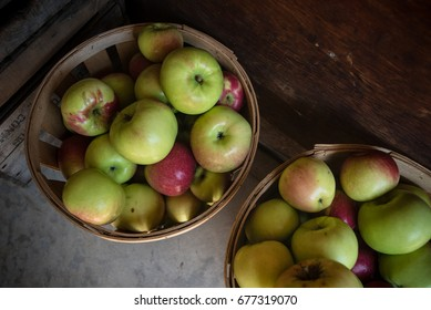 Two bushels of apples for sale at a farm stand