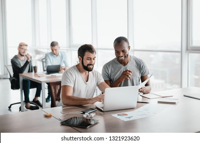 Two business colleagues discussing projects in modern office interior