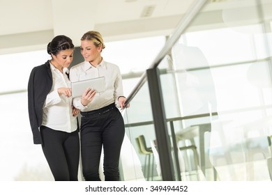Two business colleagues discussing work related matters on an office building hallway