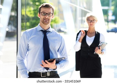 Two business colleagues in formalwear being outside.