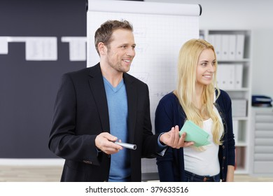 Two business colleagues giving a presentation in a meeting smiling confidently as they take questions from the audience, man and woman