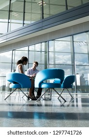 Two business colleagues sit at table in office lobby having meeting