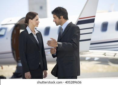 Two business colleagues standing by a plane