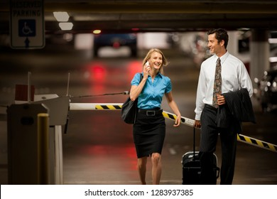 Two business colleagues walking through an underground parking lot.