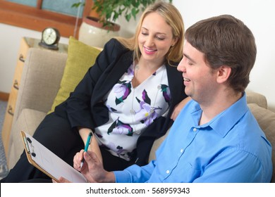 Two business colleagues, young successfull man and  attractive elegant woman, discussing some project, talking over  document, sitting in the office.