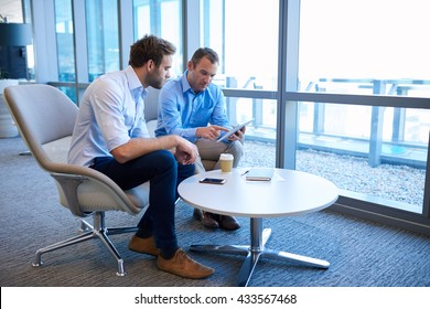 Two business entrepreneurs sitting at a coffee table together in a bright modern office space, collaborating using a digital tablet