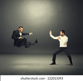 two business fighters over dark background