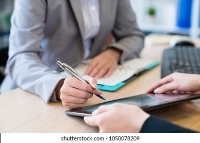 Two business lady using the tablet in the office. They are discussing the business stuff. They both wearing formal suits.