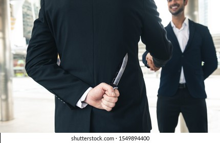 two business making handshake a deal but hiding knives or knife. Treachery risk business concept