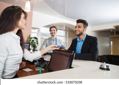 Two Business Man Arriving To Hotel Give Meeting Woman Receptionist Credit Card Pay Room Registration At Reception Counter Checking In