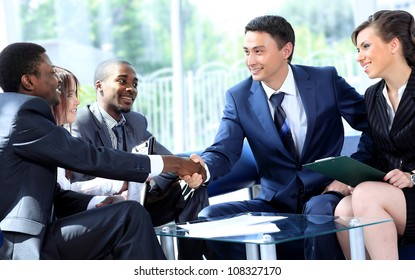Two business man shaking hands with his team in office