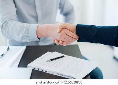 Two business man shaking hands during a meeting in the office. Documents on the table. Success deal. Dealing, greeting and partner concept. Close up