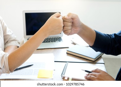 two business man woman use hand to fist bump for succes teamwork coporate