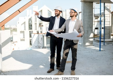 Two business men or engeneers working with house drawings on the structure during the construction process outdoors