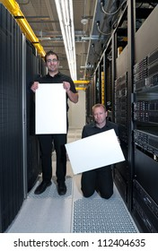 Two business men holding white blank boards in a datacenter; one with a smile and the other one with a disgruntled look
