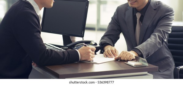 Two business men in the meeting , discussing with the paper