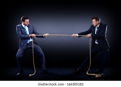 Two business men pulling rope in a competition, isolated on white background