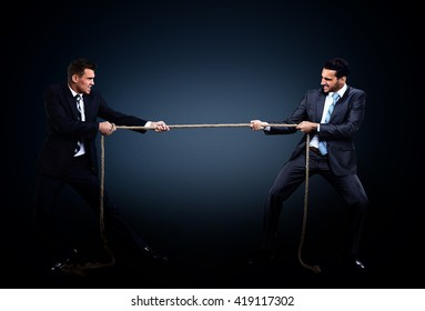 Two business men pulling rope in a competition