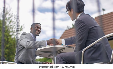 Two business men shaking hands at cafe table outdoors