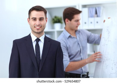 Two business men standing together in office