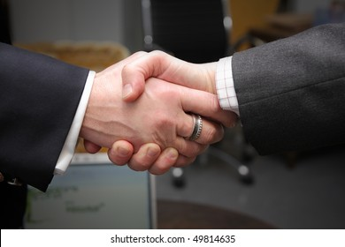 Two business men wearing suits shaking hands, closeup