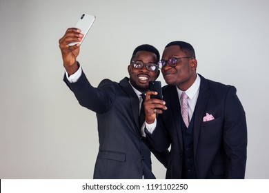 two business partner African American man taking selfie on a smartphone white background in studio. closeup portrait