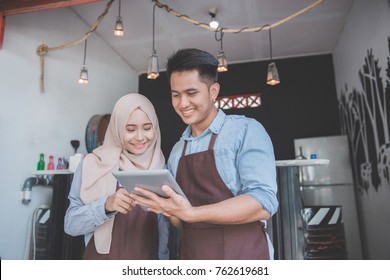 two business partner using tablet in front of their coffee shop. muslim entrepreneur concept