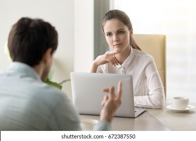 Two business partners discussing new project and sharing ideas, young serious recruiter woman listening to male candidate during job interview, female manager meeting with client at the office