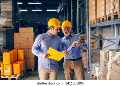 Two business partners in formal wear and with protective yellow helmets on heads standing in warehouse and comparing data. Younger holding folder while older one pointing at calculations on tablet.